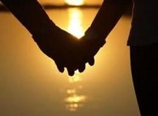 Twee handen houden elkaar vast, met op achtergrond een ondergaande zon