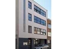 De gevel van het vlaamsoogpunt Antwerpen in de Durletstraat: een strak gebouw met nette, bleke steen en veel glaspartijen in vier verdiepingen