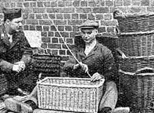 Mandenvlechter Alfons Van Gampelaere uit Wingene aan het werk, terwijl een Amerikaans soldaat hem bewondert (Tweede Wereldoorlog)