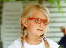 Klein meisje met vlechtjes en rode bril