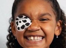 Lachend meisje; voor haar ene oog zit een wit lapje met zwarte vlekjes