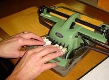 Handen typen braille met een brailleschrijfmachine