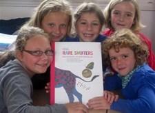 Lachende kindergezichtje rondom de cover van 'Rare snuiters'
