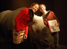 Freya en Jan met hun boek, poserend rond de kop van een vervaarlijke, maar opgezette neushoorn