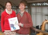 Freya en Jan met hun boek; op de achtergrond staat een giraf!