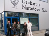 Freya en Jan met mensen van de Poolse drukkerij, poserend aan de ingang van het bedrijf