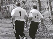 Foto van blinde atleet met begeleider; ze dragen allebei een speciaal hesje om goed herkenbaar te zijn