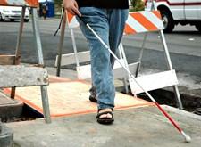 Persoon met witte stok loopt over een plank boven een werkput in het trottoir