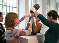 Museumbezoekers betasten een beeldje