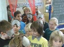 Een groepje kinderen, met of zonder blinddoek, oefent in het begeleiden of begeleid worden
