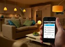 Hand houdt een smartphone vast om de huiskamerverlichting te bedienen