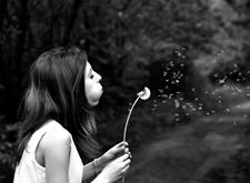Zwart-witfoto van een jonge vrouw die pluisjes uit een bol blaast