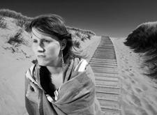 Zwart-witfoto van Deborah op het strand van Cadzand, gemaakt door Luc Dewaele; ze wandelt over een houten paadje tussen de duinen, met een doek over haar schouders tegen de wind