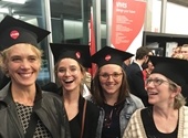 Vier van de promovendi poseren breed lachend en met een typische zwarte baret op hun hoofd