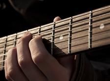Detailfoto: vingers beroeren de snaren van een gitaar, tegen een zwarte achtergrond