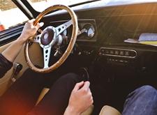 Iemand bestuurt een auto, we zien alleen de handen en knieën