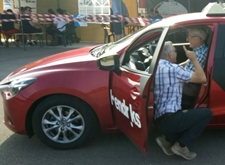 Rij-instructeur Ludo geeft uitleg over de auto, gehurkt naast de blinde chauffeur
