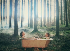 De cd-hoes van 'Warriors of the Good': de zussen CAPPAERT zitten tegenover elkaar in een badkuip, midden in een bos met hoge bomen