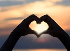 Twee handen vormen een hart, waar zonlicht door schijnt