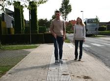 Persoon volgt ribbellijn met zijn witte stok; mobiliteitsinstructeur wandelt mee