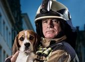 Campagnefoto 'Ik knal zonder vuurwerk', waarop een brandweerman een bange hond draagt