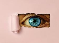 Stuk papier met uitgescheurd rechthoekje waar een oog door kijkt