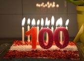 Verjaardagstaart met het getal '100' en veel brandende kaarsjes