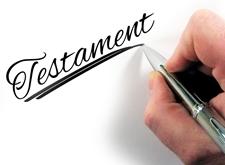 Hand met pen die 'Testament' schrijft